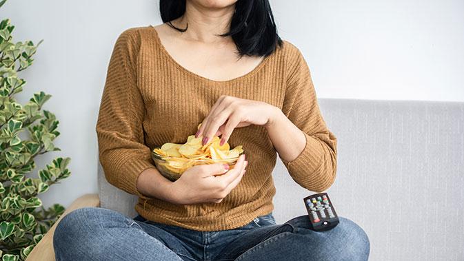 Eine Frau mit Heißhunger isst Chips auf dem Sofa.