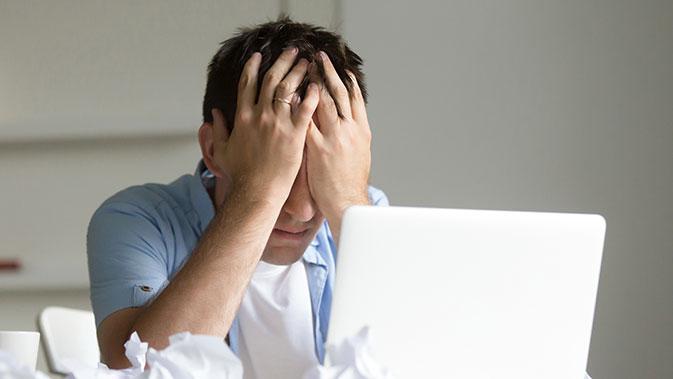 Gestresster Mann vor dem Laptop - Die Arbeit ist einer der häufigsten Gründe für Stress.