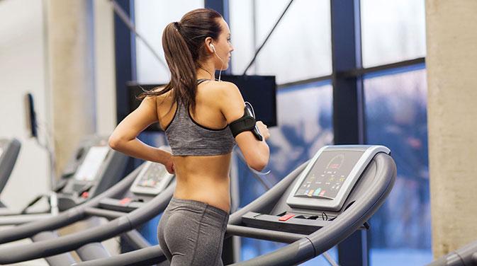Eine Frau wärmt sich auf dem Laufband auf. Mit einem lockeren Lauf kommt der Körper in Schwung und wird auf die anstehende Belastung vorbereitet.