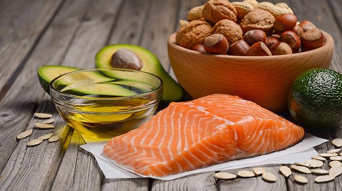 Typische Bestandteile einer ketogenen Ernährung: Gesunde Fette in Form von Nüssen, Avocado und Olivenöl sowie hochwertige Proteine, zum Beispiel als Lachsfilet.