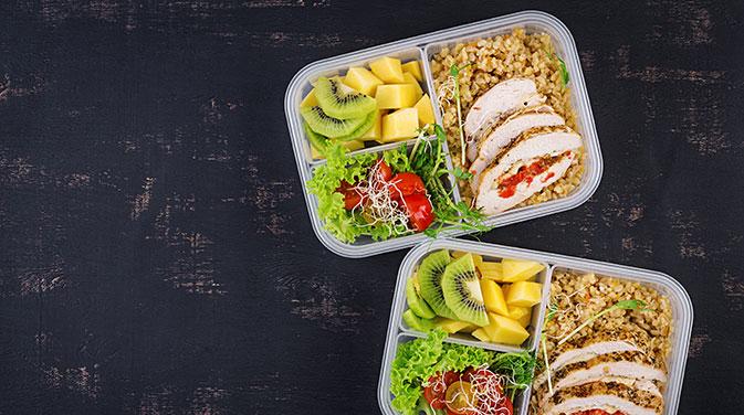 Vitamine in Form von Obst und Salat, Quinoa und eine Proteinquelle deiner Wahl lassen sich leicht vorbereiten und stellen ein ausgewogenes gesundes Mittagessen dar.
