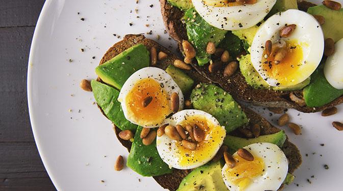 Eine Scheibe Eiweißbrot mit Ei und Avocado eignet sich bei einer ketogenen Ernährungsweise optimal als eine kleine Mahlzeit.