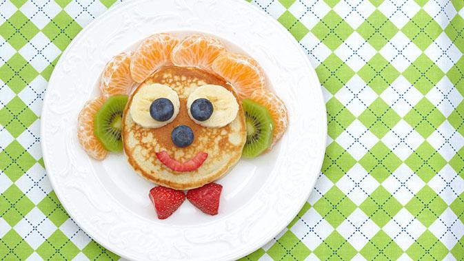 Ein bunter Teller für Kinder, bestehend aus Pfannkuchen und jede Menge Früchten.