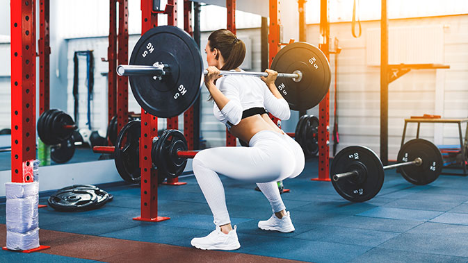 Frau macht Squats im Fitnessstudio.