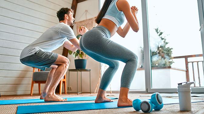 Eine Frau und ein Mann trainieren in der Wohnung.