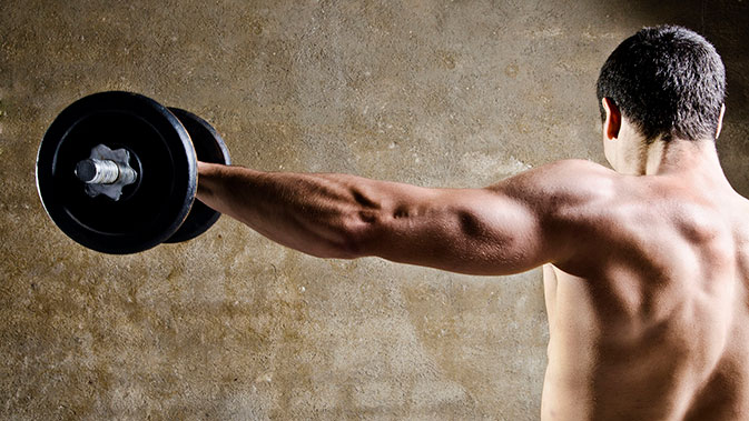 Mann trainiert seine Schulter mit einer Kurzhantel