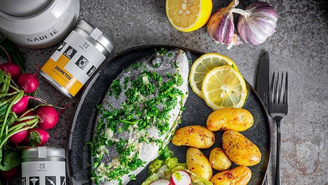 Mahlzeit bestehend aus gegrilltem Fisch, Kartoffeln und Salat.