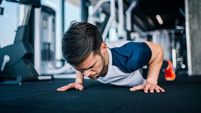 Mann macht Push-Ups im Fitnessstudio