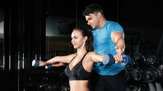 Trainer gibt einer jungen Frau Hilfestellung beim Seitheben.