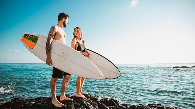 Zwei Surfer mit Surfbrettern am Meer