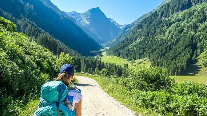 Frau mit Rucksack auf einem Wanderweg in den Bergen