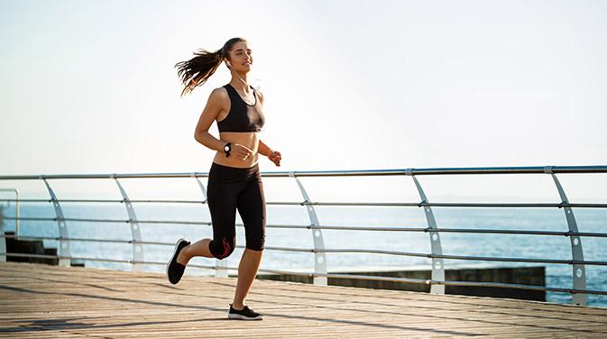 Frau joggt an der Promenade entlang