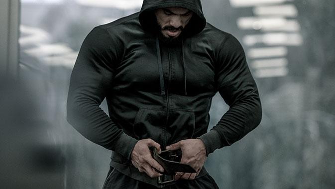 Fokussierter Mann mit Hoodie im Fitnessstudio.